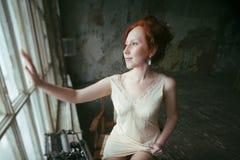 Mujer del jengibre de la belleza en la ventana, viejo interior de la casa Foto de archivo