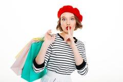 Mujer del jengibre del misterio que lleva a cabo los paquetes y que muestra gesto secreto imagenes de archivo