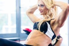 Mujer del levantamiento de pesas que hace abdominales en gimnasio de la aptitud Imágenes de archivo libres de regalías