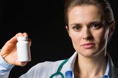 Mujer del médico que muestra la botella de la medicina Imagenes de archivo