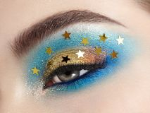 Mujer del maquillaje del ojo con las estrellas decorativas foto de archivo