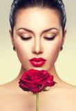 Mujer del modelo de moda de la belleza con la flor de la rosa del rojo Fotos de archivo libres de regalías