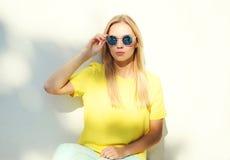 Mujer del modelo de moda del retrato en gafas de sol y camiseta amarilla Fotos de archivo