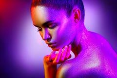 Mujer del modelo de moda en chispas brillantes coloridas y luces de neón que presentan en el estudio, retrato de la muchacha atra imagen de archivo libre de regalías