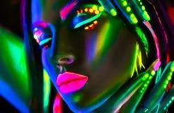 Mujer del modelo de moda en la luz de neón Muchacha modelo hermosa con maquillaje fluorescente colorido foto de archivo