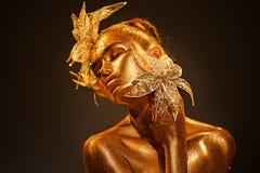 Mujer del modelo de moda en las chispas de oro brillantes coloridas que presentan con la flor de la fantasía fotografía de archivo libre de regalías