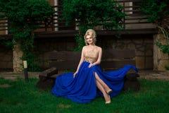 Mujer del modelo de moda que presenta el vestido de noche largo atractivo, que lleva imagen de archivo