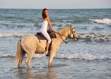 Mujer del montar a caballo en el mar Fotografía de archivo