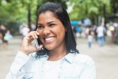 Mujer del nativo americano que habla en el teléfono en un parque Fotografía de archivo