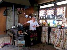 Mujer del Nepali que cocina en su casa de campo Himalayan Foto de archivo libre de regalías