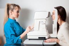 Mujer del oftalmólogo en sitio del examen con morenita hermosa joven imagen de archivo libre de regalías