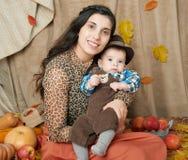 Mujer del otoño con el niño pequeño en las hojas amarillas de la caída, manzanas, calabaza y decoración en la materia textil, fam Imagen de archivo libre de regalías