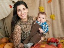 Mujer del otoño con el niño pequeño en las hojas amarillas de la caída, manzanas, calabaza y decoración en la materia textil, fam Fotografía de archivo libre de regalías