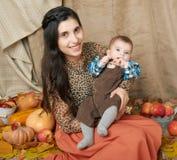 Mujer del otoño con el niño pequeño en las hojas amarillas de la caída, manzanas, calabaza y decoración en la materia textil, fam Foto de archivo