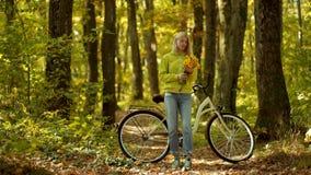 Mujer del otoño con la bici retra con las flores en cesta en parque otoñal Muchacha feliz y alegr?a del oto?o Mujer despreocupada metrajes