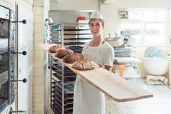 Mujer del panadero que presenta el pan a bordo en panadería imágenes de archivo libres de regalías