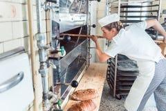Mujer del panadero que sale el pan del horno de panadería Foto de archivo libre de regalías