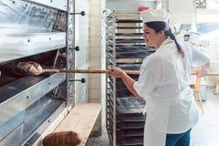 Mujer del panadero que sale el pan del horno de panadería foto de archivo