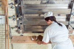 Mujer del panadero que sale los panes del pan del horno de panadería Fotos de archivo
