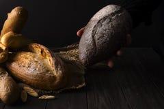 Mujer del panadero que sostiene la barra de pan orgánica rústica en manos - panadería rural Luz natural, aún vida cambiante Fotos de archivo