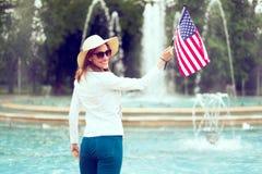 Mujer del patriota que sostiene la bandera de los E.E.U.U. en la vista posterior del parque que considera detrás el Día de la Ind foto de archivo