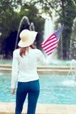Mujer del patriota que sostiene la bandera de los E.E.U.U. en vista posterior del parque imagen de archivo libre de regalías