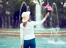 Mujer del patriota que sostiene la bandera de los E.E.U.U. que mira para arriba, en vista posterior del parque imagen de archivo libre de regalías