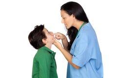 Mujer del pediatra que hace un chequeo para el niño Imagenes de archivo