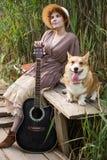 Mujer del pelirrojo con el perro de la guitarra y del corgi en campo Fotografía de archivo libre de regalías