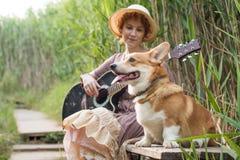 Mujer del pelirrojo con el perro de la guitarra y del corgi en campo Imagen de archivo libre de regalías