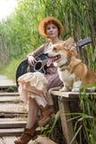 Mujer del pelirrojo con el perro de la guitarra y del corgi en campo Imagenes de archivo