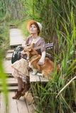 Mujer del pelirrojo con el perro de la guitarra y del corgi en campo Foto de archivo