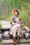 Mujer del pelirrojo con el perro de la guitarra y del corgi en campo Imágenes de archivo libres de regalías