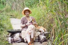 Mujer del pelirrojo con el perro de la guitarra y del corgi en campo Fotos de archivo