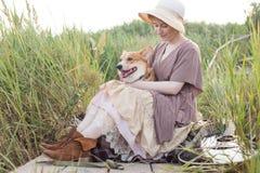 Mujer del pelirrojo con el perro de la guitarra y del corgi en campo Fotografía de archivo