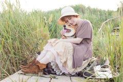 Mujer del pelirrojo con el perro de la guitarra y del corgi en campo Imagen de archivo