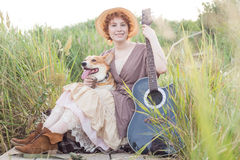 Mujer del pelirrojo con el perro de la guitarra y del corgi en campo Foto de archivo libre de regalías