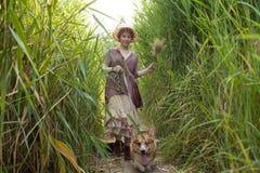 Mujer del pelirrojo con el perro del corgi en campo Fotos de archivo