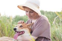 Mujer del pelirrojo con el perro del corgi en campo Imágenes de archivo libres de regalías