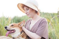 Mujer del pelirrojo con el perro del corgi en campo Fotos de archivo libres de regalías