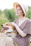 Mujer del pelirrojo con el perro del corgi en campo Foto de archivo