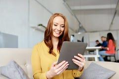 Mujer del pelirrojo con la PC de la tableta que trabaja en la oficina imagenes de archivo