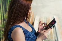 Mujer del pelirrojo con la tableta al aire libre Foto de archivo