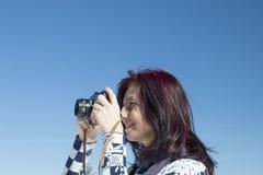 Mujer del pelirrojo con una cámara vieja Foto de archivo libre de regalías