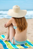 Mujer del pelirrojo en bikini y Sunhat en la playa foto de archivo