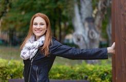 Mujer del pelirrojo en la chaqueta de cuero que presenta en parque en el otoño Imagenes de archivo