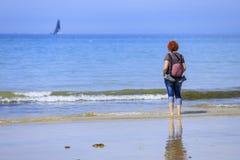 Mujer del pelirrojo en la costa fotos de archivo