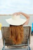 Mujer del pelirrojo en Straw Hat On Deck Chair fotos de archivo