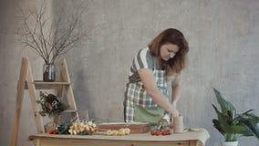 Mujer del pelirrojo que arregla el arreglo comestible del ramo almacen de metraje de vídeo