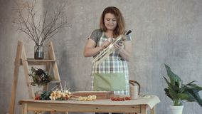 Mujer del pelirrojo que arregla el ramo comestible en el lugar de trabajo metrajes